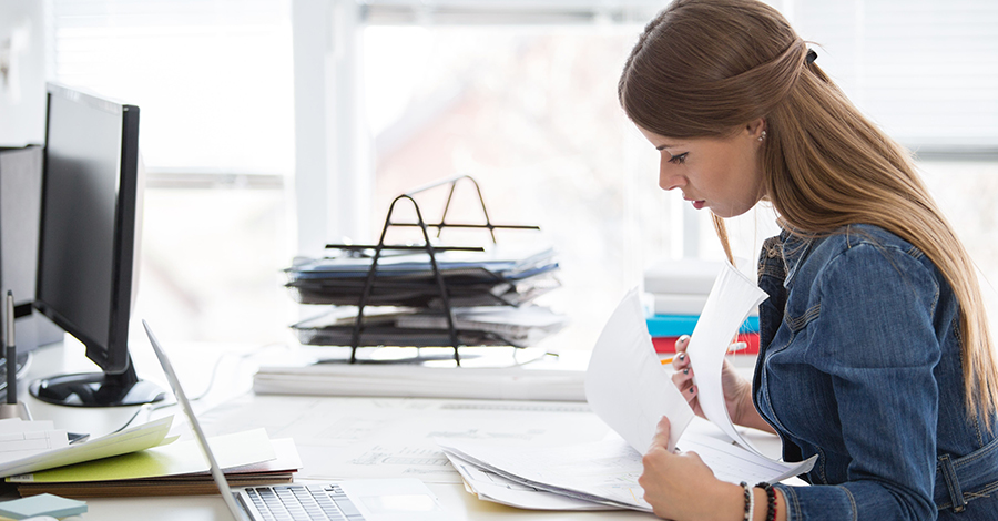Business woman reading invoices at her desk