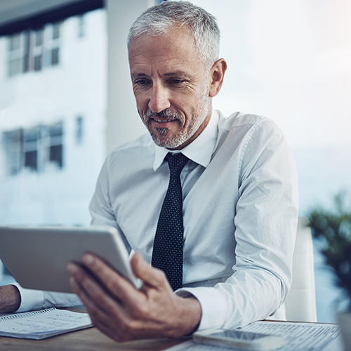 Middle aged man sitting with an ipad at his desk