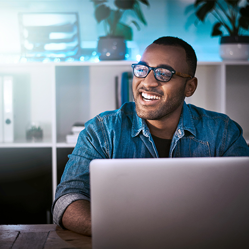 Man sitting behind a computer looking happy